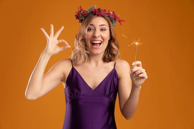 茶色の背景に分離された大丈夫なジェスチャーを示す線香花火を保持している花輪と紫色のドレスを着てうれしそうな若い美しい少女