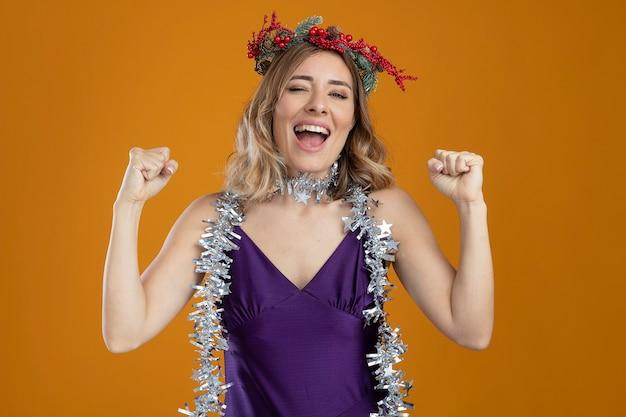 갈색 배경에 고립 예 제스처를 보여주는 화 환과 보라색 드레스를 입고 즐거운 젊은 아름 다운 소녀
