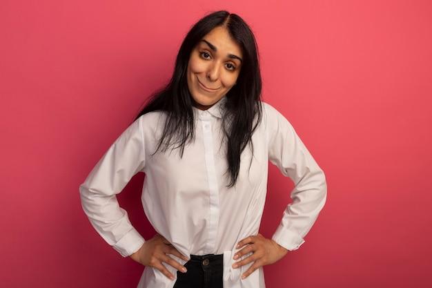 Gioiosa giovane bella ragazza che indossa la maglietta bianca che mette le mani sull'anca isolata sul colore rosa
