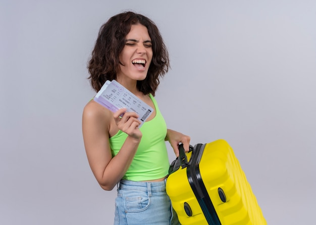 Joyful young beautiful traveler woman holding airplane tickets and suitcase on isolated white wall
