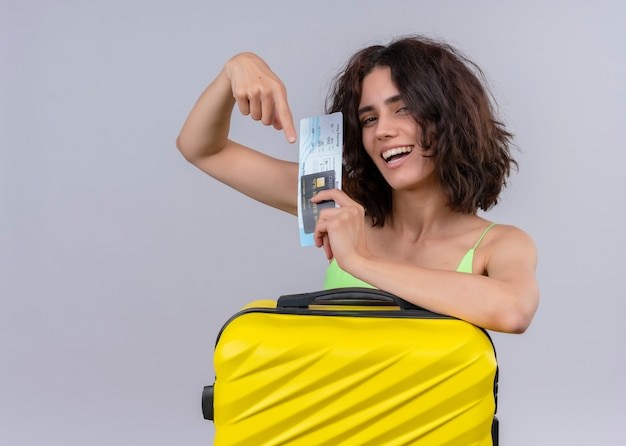 Joyful young beautiful traveler woman holding card, airplane tickets and suitcase and pointing at them on isolated white wall