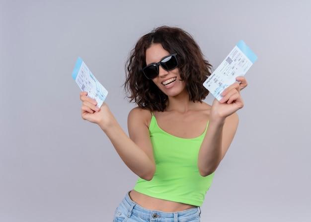 Радостная молодая красивая женщина-путешественница в солнцезащитных очках и держит билеты на самолет на изолированной белой стене