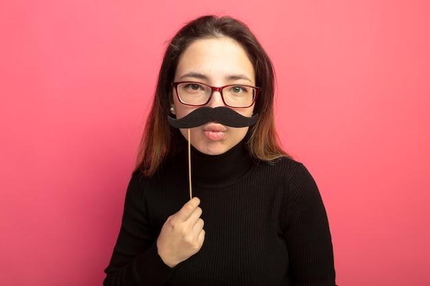 Gioiosa giovane bella donna in un dolcevita nero e occhiali che tengono i baffi divertenti sul bastone in piedi sopra la parete rosa