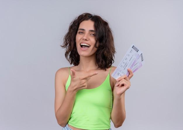 Радостная молодая красивая женщина держит билеты на самолет и указывая на них на изолированной белой стене