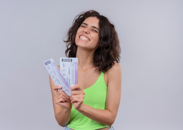 Joyful young beautiful woman holding airplane tickets on isolated white wall with copy space