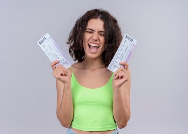 Радостная молодая красивая женщина, держащая билеты на самолет на изолированной белой стене