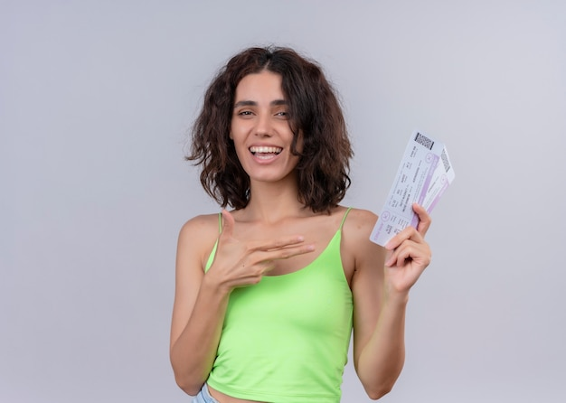 Joyful young beautiful woman holding airplane tickets and pointing at them on isolated white wall