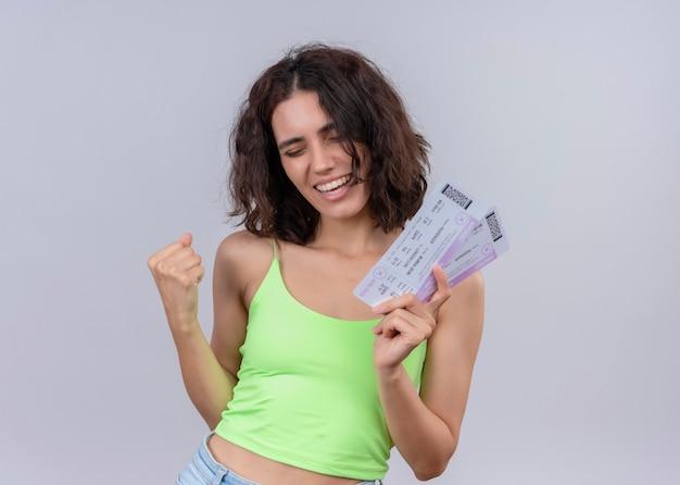 Радостная молодая красивая женщина, держащая билеты на самолет сжатым кулаком на изолированной белой стене