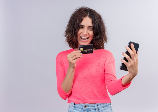 コピースペースと分離の白い壁にカードと携帯電話を保持してうれしそうな若い美しい女性