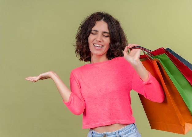 紙袋を押しながら孤立した緑の壁に空の手を示すうれしそうな若い美しい女性