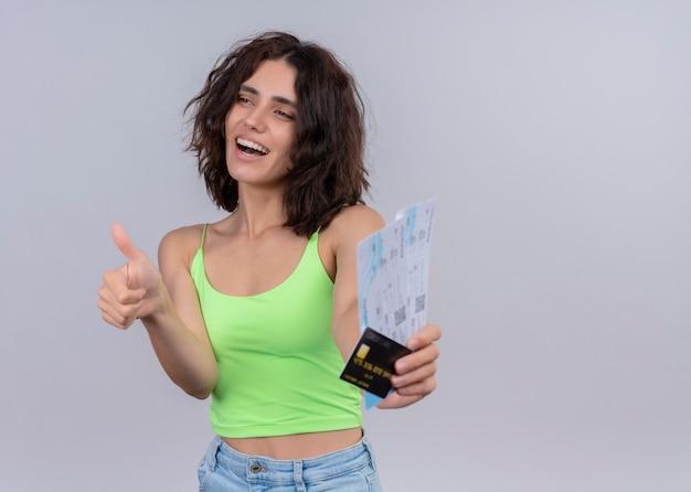 Радостная молодая красивая женщина протягивает билеты на самолет и открытку и показывает палец вверх на изолированной белой стене с копией пространства