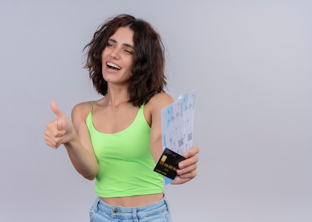 Joyful young beautiful woman stretching airplane tickets and card and showing thumb up on isolated white wall with copy space