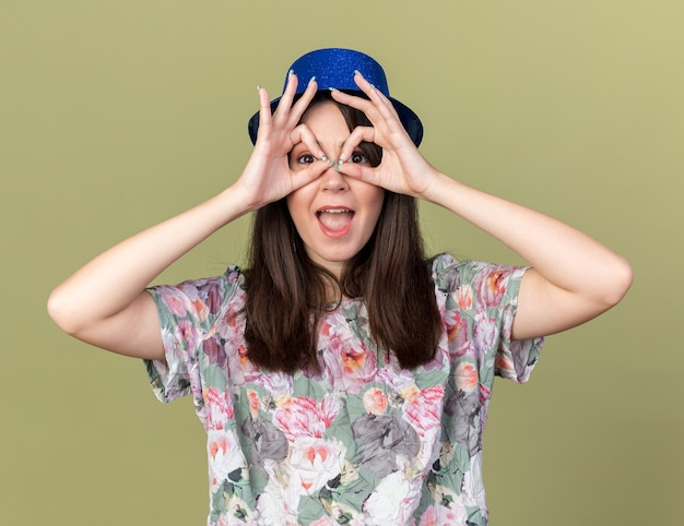 Joyful young beautiful woman wearing party hat showing look gesture isolated on olive green wall