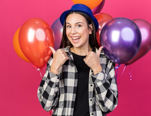 ピンクの壁に分離された親指を示す前の風船に立っているパーティーハットを身に着けているうれしそうな若い美しい女性