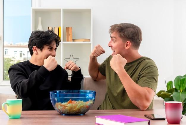 うれしそうな若いブロンドとブルネットのハンサムな男は、拳を保ち、お互いを見ながらテーブルに座っています