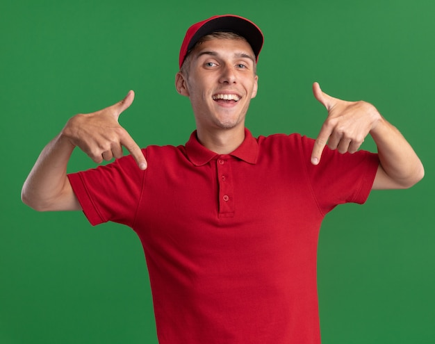 Joyful young blonde delivery boy points down with two hands