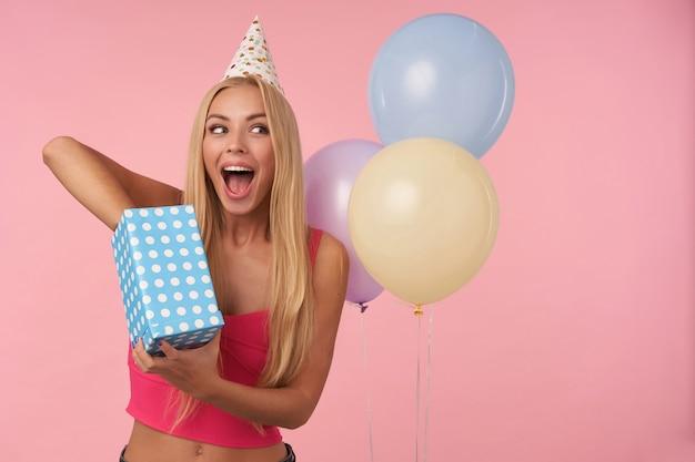 Gioiosa giovane femmina bionda con i capelli lunghi in posa su sfondo rosa mentre disimballano i regali, essendo eccitata e sorpresa di ricevere regali di compleanno. attributi di persone, intrattenimento e vacanza