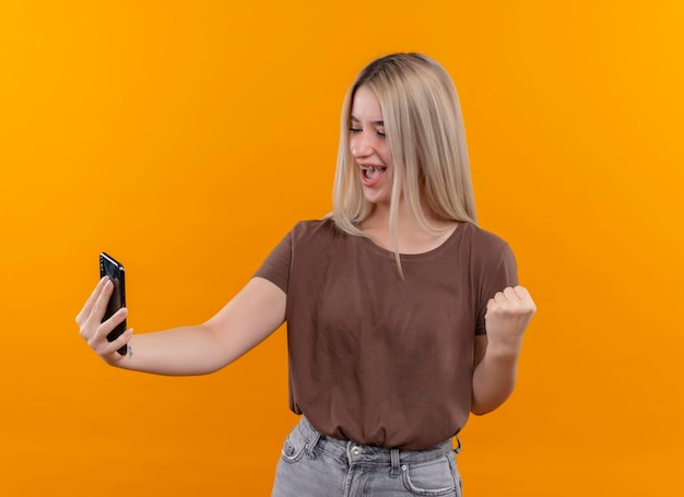 Joyful young blonde girl in dental braces holding mobile phone looking at it with raised fist on isolated orange space with copy space