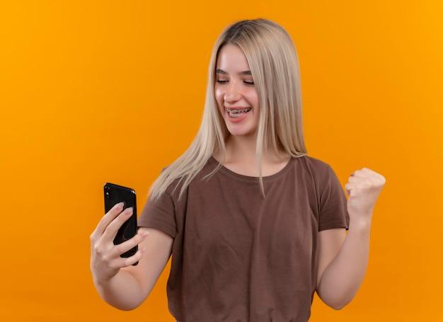 Gioiosa giovane ragazza bionda in parentesi graffe dentali tenendo il telefono cellulare e guardandolo con il pugno alzato sullo spazio arancione isolato