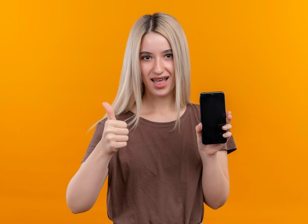 Gioiosa giovane ragazza bionda in parentesi graffe dentali tenendo il telefono cellulare che mostra il pollice in alto sullo spazio arancione isolato con spazio di copia