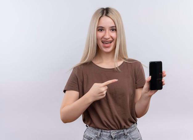 Gioiosa giovane ragazza bionda in parentesi graffe dentali holding e indicando il telefono cellulare su uno spazio bianco isolato con spazio di copia