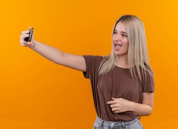 Gioiosa giovane ragazza bionda in parentesi graffe dentali tenendo selfie su uno spazio arancione isolato