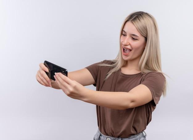 Gioiosa giovane ragazza bionda in parentesi graffe dentali prendendo selfie su uno spazio bianco isolato