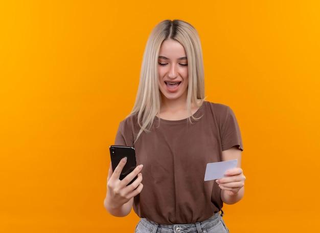 Радостная молодая блондинка в брекетах держит мобильный телефон и кредитную карту на изолированном оранжевом пространстве с копией пространства