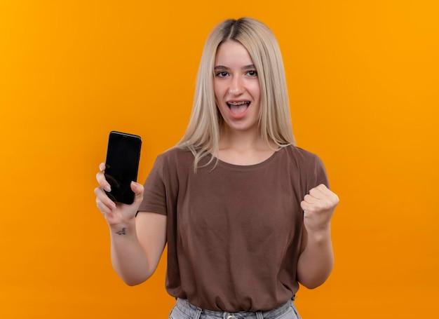 コピースペースと孤立したオレンジ色のスペースに上げられた握りこぶしで携帯電話を保持している歯科ブレースでうれしそうな若いブロンドの女の子