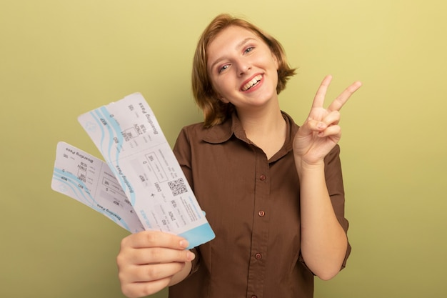 平和のサインをやって飛行機のチケットを伸ばすうれしそうな若いブロンドの女の子