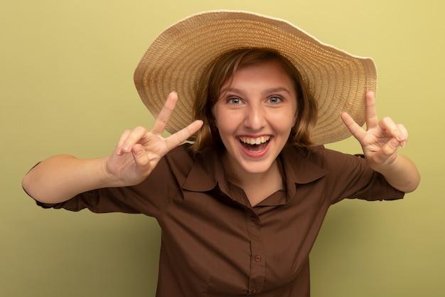 オリーブグリーンの壁に分離された平和のサインをやってビーチ帽子をかぶってうれしそうな若いブロンドの女の子