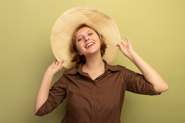 Joyful young blonde girl wearing beach hat grabbing hat  isolated on olive green wall