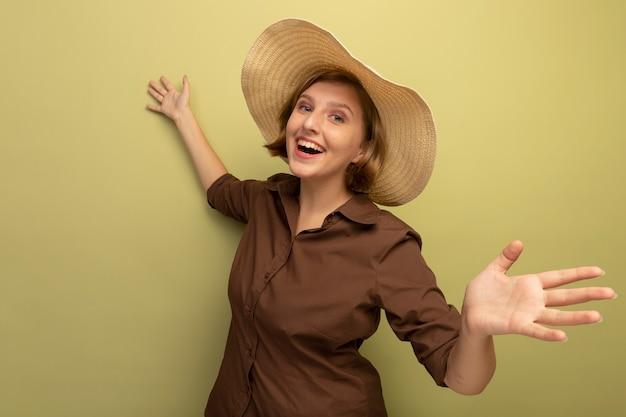 コピースペースでオリーブグリーンの壁に孤立して見える手を伸ばしてビーチ帽子をかぶってうれしそうな若いブロンドの女の子