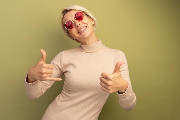 선글라스를 끼고 느슨한 몸짓을 하고 복사 공간이 있는 올리브 녹색 벽에 고립된 엄지손가락을 보여주는 즐거운 금발 소녀