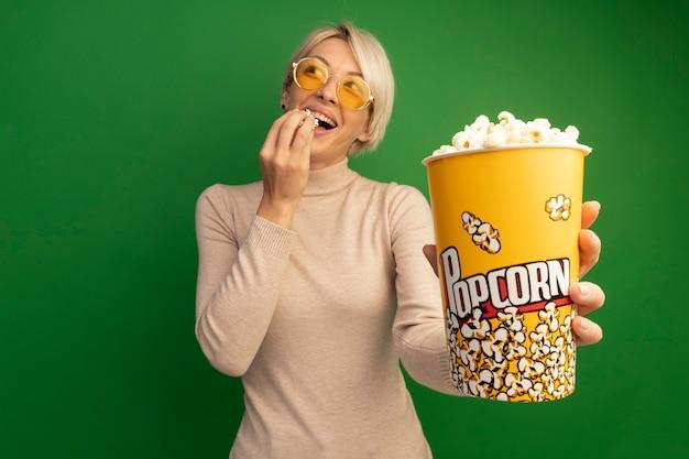 Gioiosa ragazza bionda che indossa occhiali da sole che allunga il secchio di popcorn e pezzi di popcorn vicino alla bocca guardando il lato isolato sulla parete verde con spazio di copia