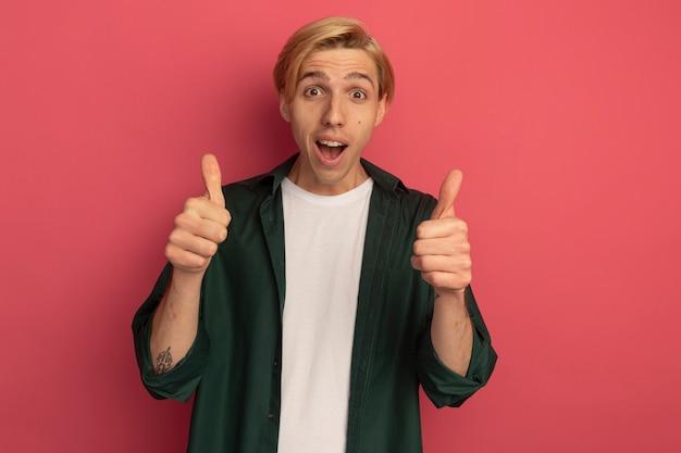 親指を立てて緑のtシャツを着てうれしそうな若いブロンドの男