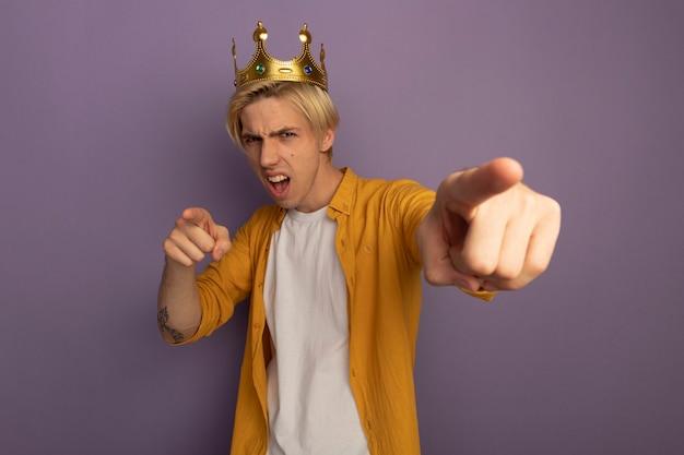 Gioioso giovane ragazzo biondo che indossa maglietta gialla e corona che ti mostra gesto isolato sulla porpora