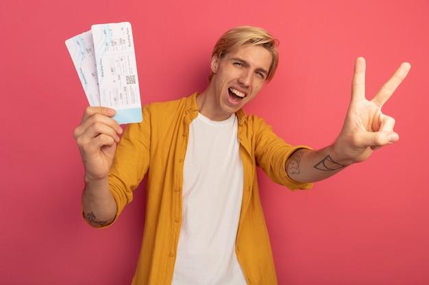 Gioioso giovane ragazzo biondo che indossa la maglietta gialla che tiene i biglietti che mostrano gesto di pace