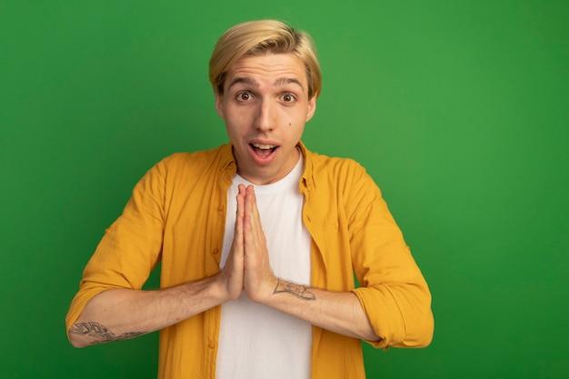복사 공간 녹색에 고립 된기도 제스처를 보여주는 노란색 티셔츠를 입고 즐거운 젊은 금발의 남자