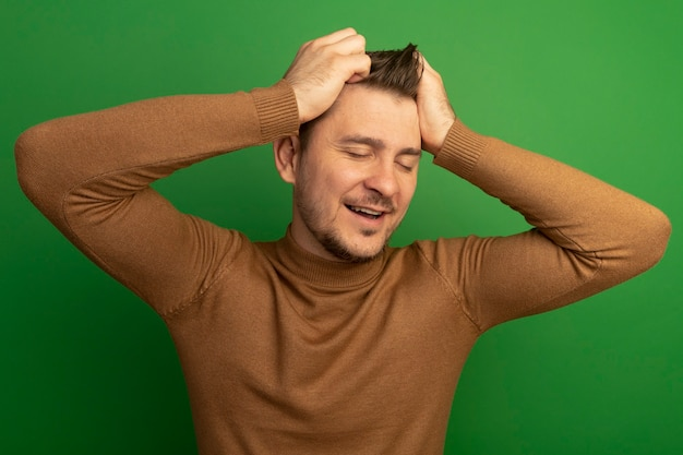 Joyful young blonde handsome man putting hands on head with closed eyes isolated on green wall