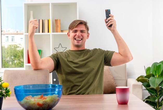 Gioiosa giovane bionda bell'uomo si siede al tavolo con una ciotola di patatine e tazza tenendo il telecomando della tv e alzando il pugno