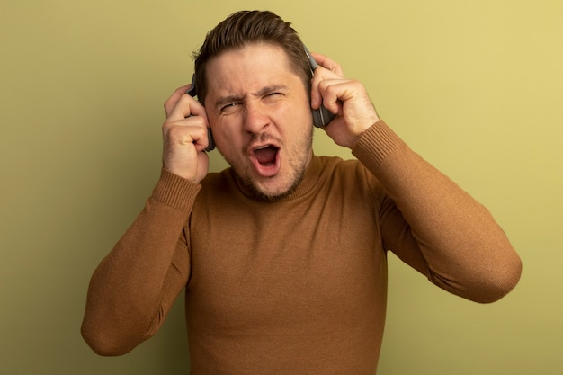 Joyful young blonde handsome man wearing and grabbing headphones enjoying music