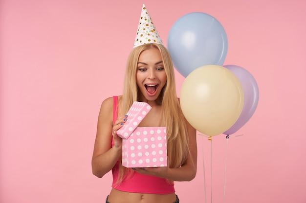ピンクの背景の上に色とりどりの気球でポーズをとり、目と口を大きく開いたまま、プレゼントを開梱し、内容に驚いている長い髪のうれしそうな若いブロンドの女性