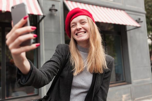 Gioiosa giovane donna bionda dai capelli lunghi in abiti eleganti, tenendo il cellulare in mano alzata e sorridente ampiamente mentre si fa selfie
