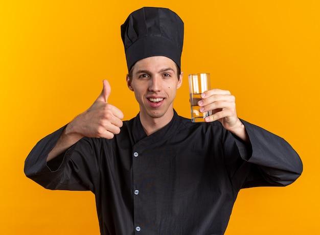 Gioioso giovane cuoco maschio biondo in uniforme da chef e berretto con in mano un bicchiere d'acqua che mostra il pollice in su