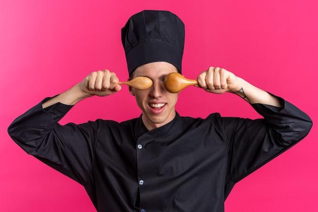 Gioioso giovane maschio biondo cuoco in uniforme da chef e cappello che tiene i cucchiai davanti agli occhi