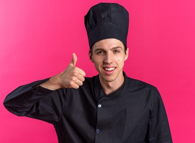 Giovane cuoco maschio biondo allegro in uniforme da chef e cappuccio che mostra pollice in su
