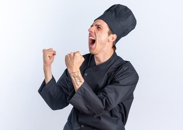 Gioioso giovane maschio biondo cuoco in uniforme da chef e berretto in piedi in vista di profilo guardando il lato facendo sì gesto
