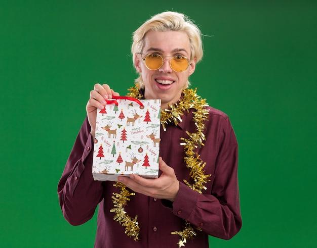 Радостный молодой блондин в очках с гирляндой из мишуры на шее держит рождественский подарочный пакет, изолированный на зеленой стене
