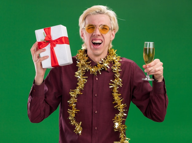 Gioioso giovane uomo biondo che indossa occhiali con ghirlanda di orpelli intorno al collo tenendo un bicchiere di champagne e pacchetto regalo guardando la telecamera urlando isolato su sfondo verde
